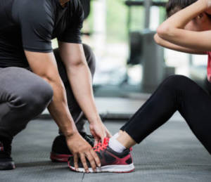 Trainer holding woman's feet as she completes a sit-up