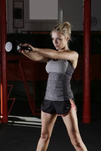 Blonde woman lifting a weight in a gym